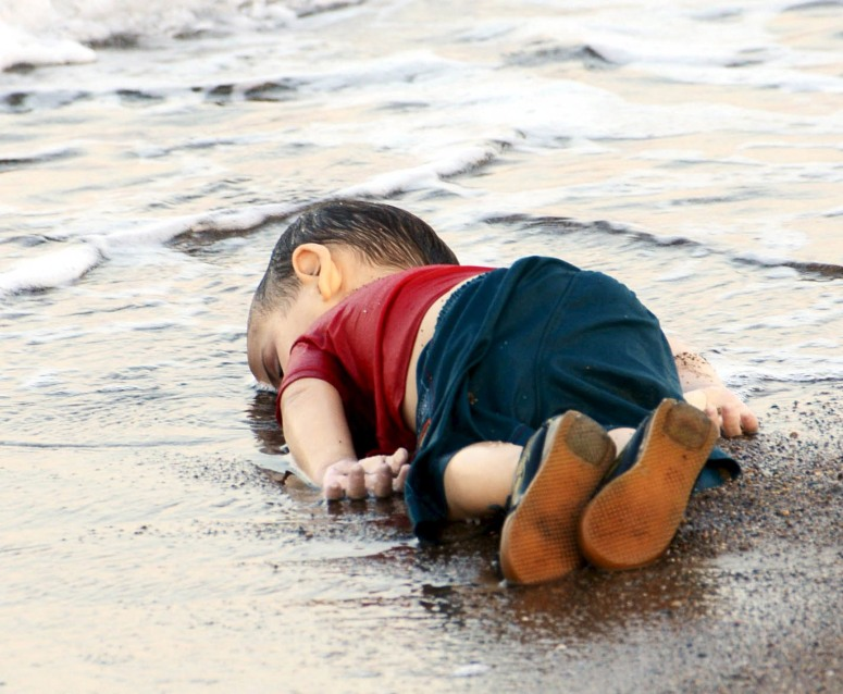 A young migrant, who drowned in a failed attempt to sail to the Greek island of Kos, lies on the shore in the Turkish coastal town of Bodrum