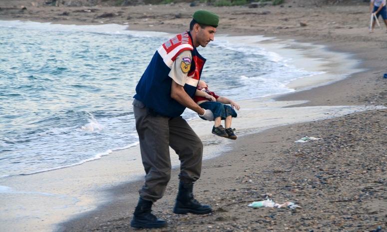 警員抱走幼童遺體,面容極為沉重。該照片立即在Twitter被標上 #KiyiyaVuranInsanlik(人被沖到岸上之意)瘋傳。